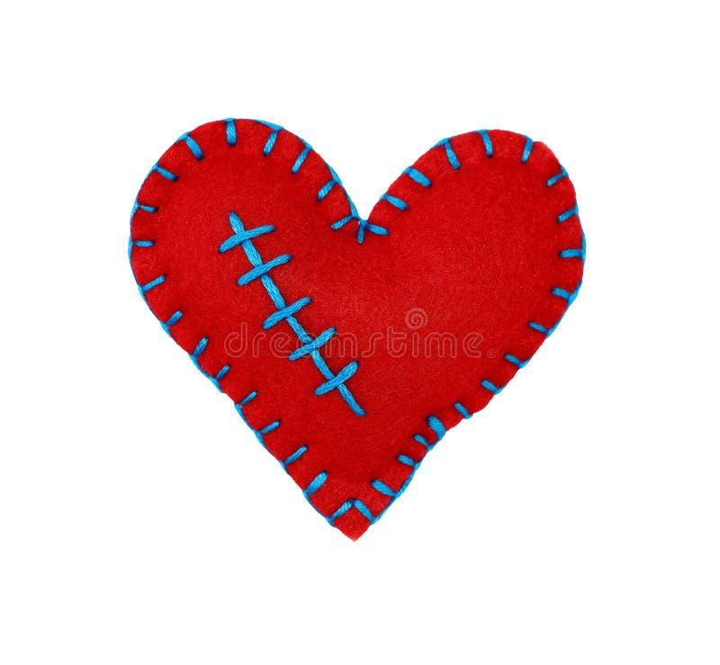 Un corazón cosido sentido rojo aislado en blanco imagen de archivo libre de regalías