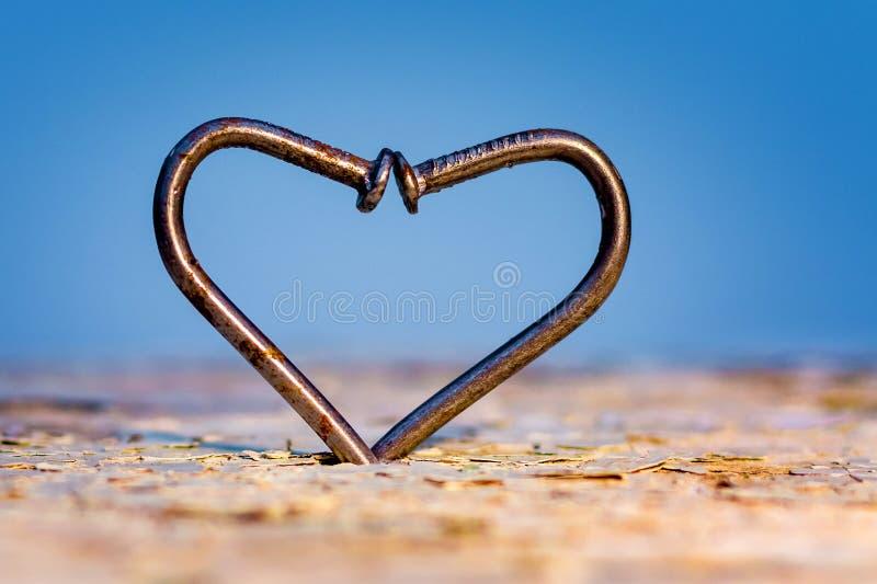 Un corazón de clavos curvados en un fondo azul, un símbolo del overco imágenes de archivo libres de regalías