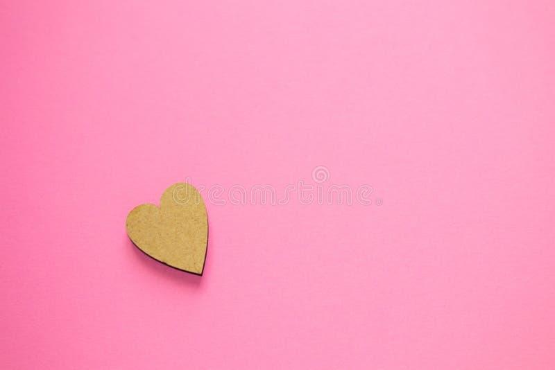 Un corazón de madera en fondo rosado con el espacio de la copia para el texto Concepto de amor, el día de tarjeta del día de San  fotografía de archivo libre de regalías