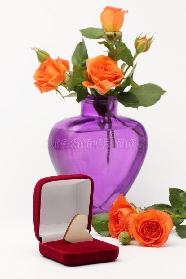 Un corazón de madera y un florero de rosas imagen de archivo