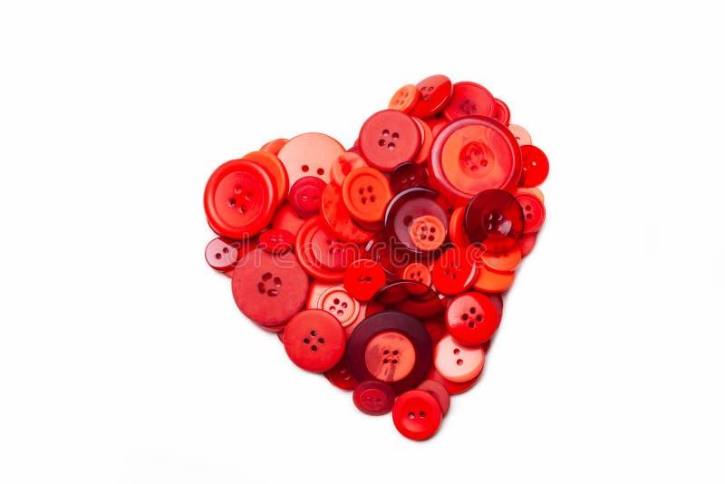 Un corazón formado con los botones rojos diversos fotografía de archivo