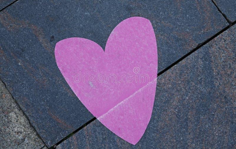 Un corazón rosado en el pavimento imagen de archivo libre de regalías