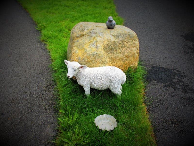 Un cordero en porcelana en el jardín, mientras que un pato en piedra para arriba en una piedra la cabe fotos de archivo libres de regalías
