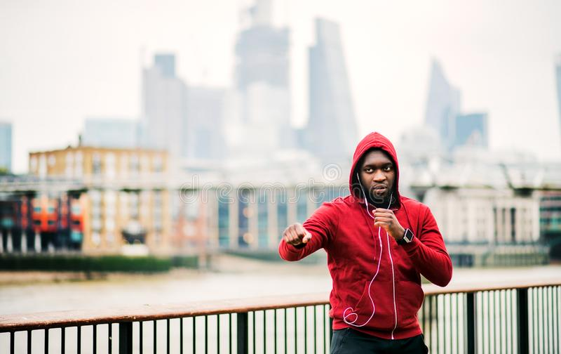 Un corredor del hombre negro con los auriculares y la capilla en su cabeza en una ciudad Copie el espacio fotos de archivo