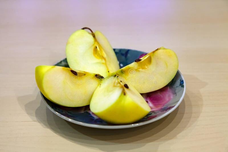 Un corte verde de la manzana en cuatro pedazos en una placa coloreada después del harv imagen de archivo libre de regalías