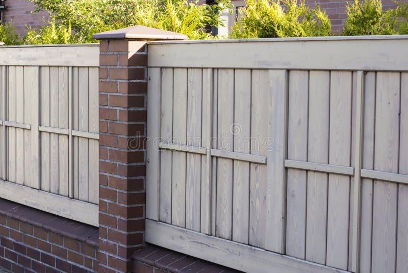 Un cortile soleggiato piacevole con erba verde e un recinto di legno piacevole immagini stock libere da diritti