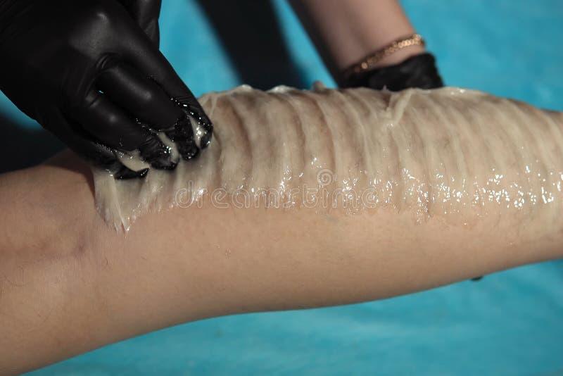Un cosmetologist enlève des cheveux des jambes d'une pâte de sucre de jeune femme image libre de droits