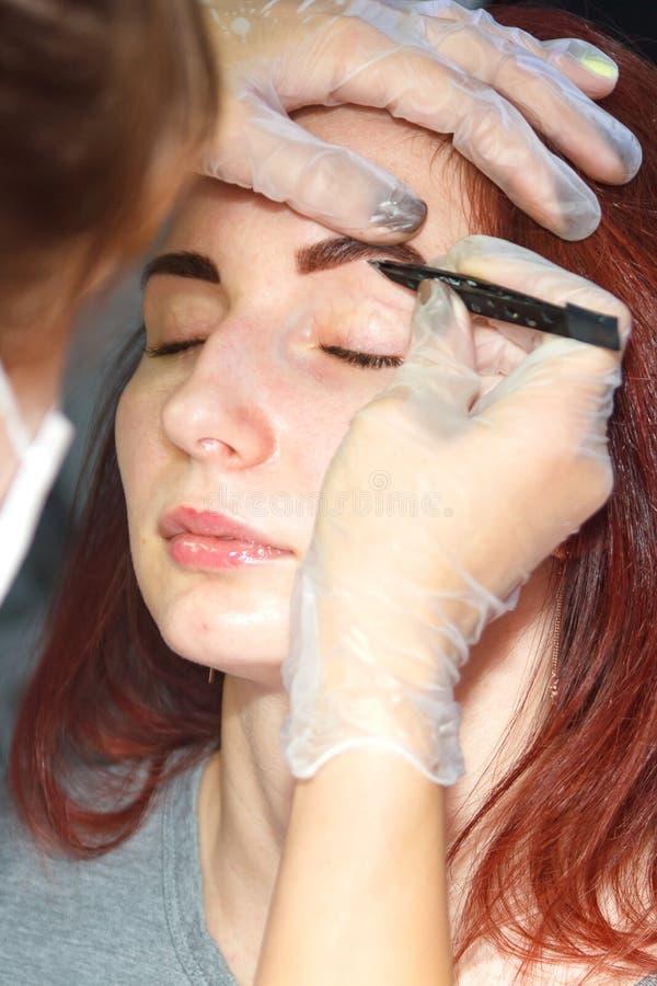 Un cosmetologist enlève les poils excédentaires de sourcil sur un client après la souillure avec des brucelles photo libre de droits