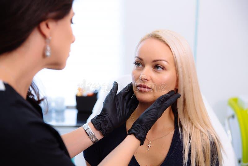 Un cosmetologist lleva a cabo las manos y examina la cara de una mujer antes de realizar procedimientos La muchacha en la recepci imagen de archivo