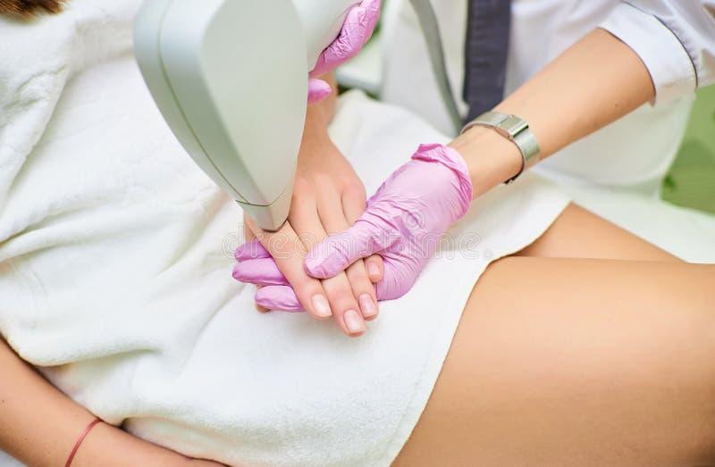 Un cosmetologo effettua una procedura per depilazione del laser dal corpo di una ragazza fotografia stock libera da diritti