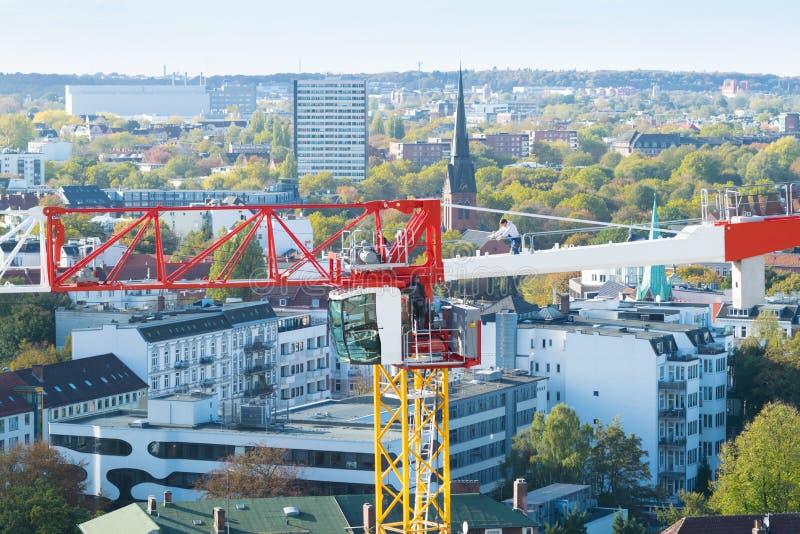 Un costruttore sopra una gru a torre sopra la città di Amburgo immagine stock