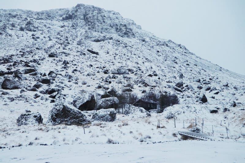 Un cottage islandese sotto la collina fotografia stock libera da diritti