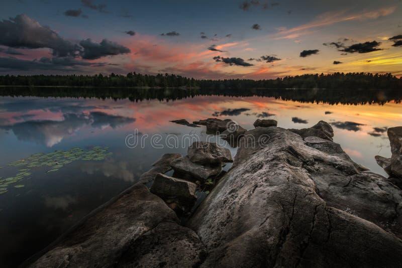 Un coucher de soleil avec des nuages a réfléchi sur un lac lisse photo stock