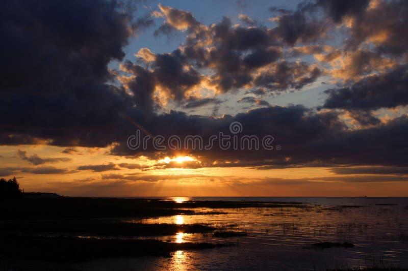Un coucher du soleil coloré et les nuages foncés au-dessus de la mer images stock
