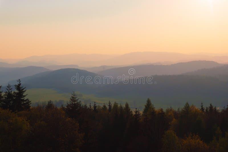 Un coucher du soleil jaunâtre gentil dans les montagnes photographie stock