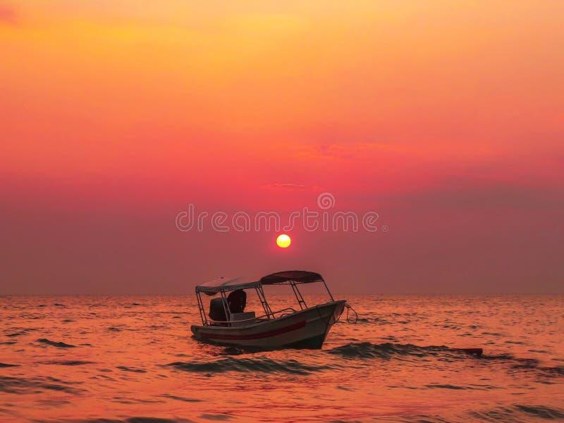 Un coucher du soleil paisible au-dessus d'un bateau dans le port Dickson photographie stock