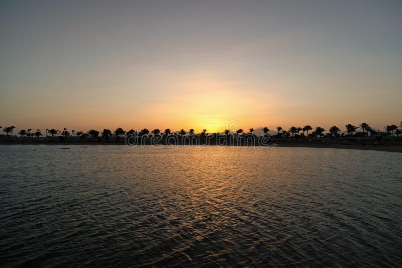 Un coucher du soleil plus parfait Le coucher du soleil sur la c?te avec des palmiers et la r?flexion du soleil arrosent Silhouett photo libre de droits