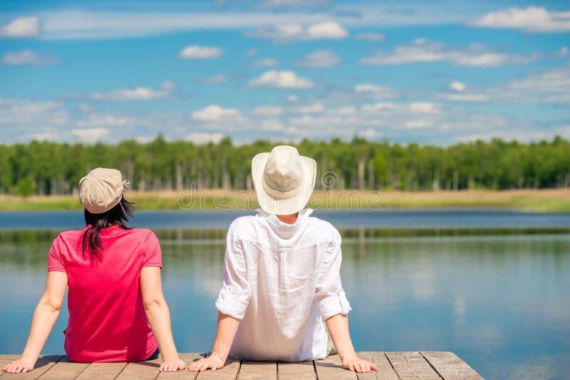 Un couple affectueux appréciant un beau lac se reposant sur pi en bois images stock