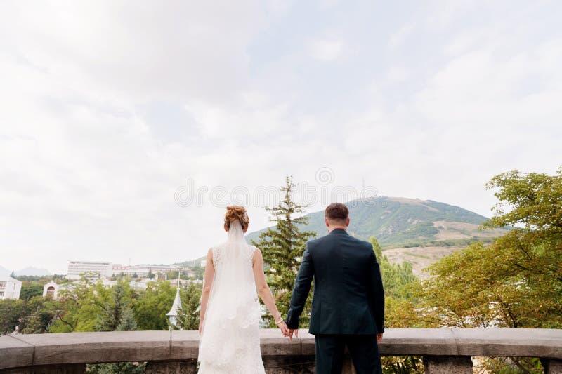 Un couple affectueux des nouveaux mariés se tient tenant des mains et les embrassant dans la perspective du paysage de ville du images stock