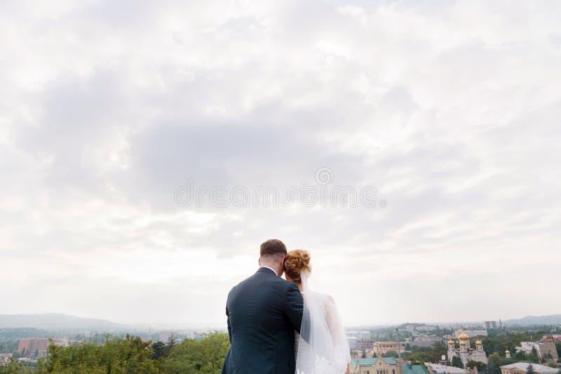 Un couple affectueux des nouveaux mariés se tient tenant des mains et les embrassant dans la perspective du paysage de ville du images libres de droits