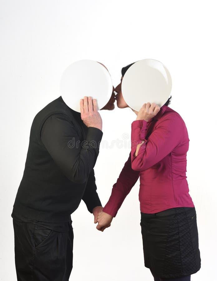 Un couple affectueux s'embrassant caché derrière image libre de droits
