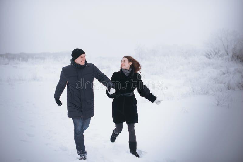 Un couple affectueux sur une promenade d'hiver Histoire d'amour de neige, magie d'hiver Homme et femme sur la rue givrée Le type  image stock