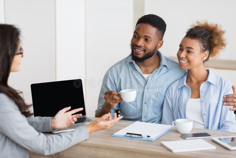Un couple afro-américain assiste à une consultation sur l'achat d'une maison dans une agence immobilière photographie stock libre de droits