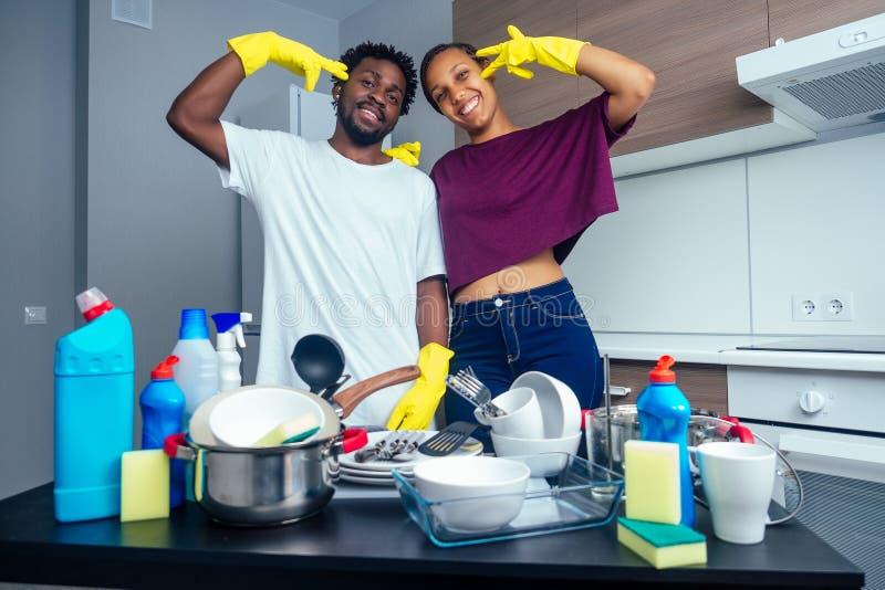 Un couple afro-américain fatigué et fatigué, près de la table, rempli de assiettes et de tasses sales photo stock