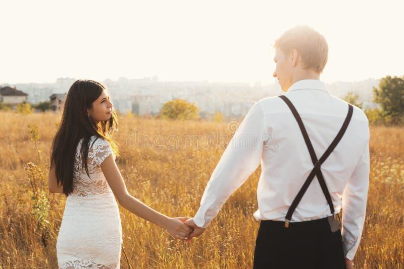Un couple appréciant une promenade, tenant des mains, avec la ville sur ho image libre de droits
