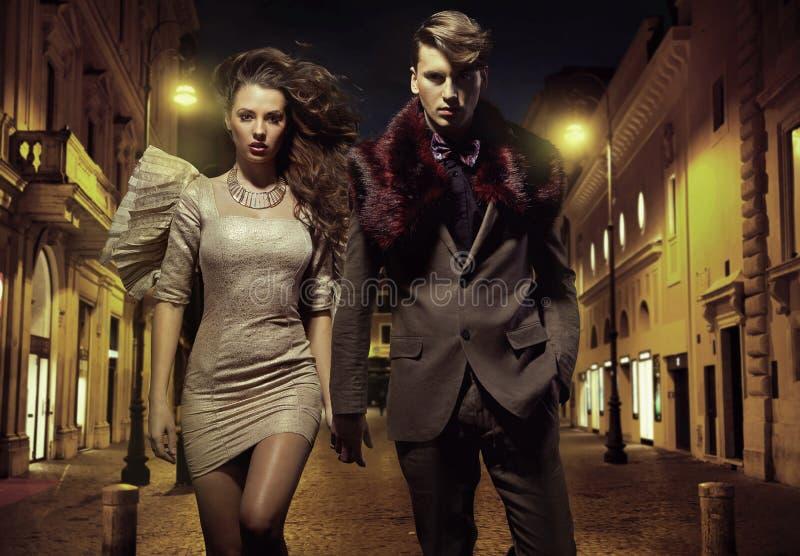 Un couple attrayant marchant au centre ville photographie stock libre de droits