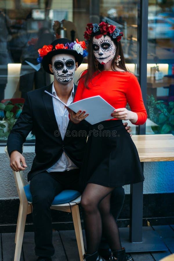 Un couple, crâne de port compenser Tout le jour d'âmes Maquillage de crâne de sucre de garçon et de fille peint pour Halloween re images stock
