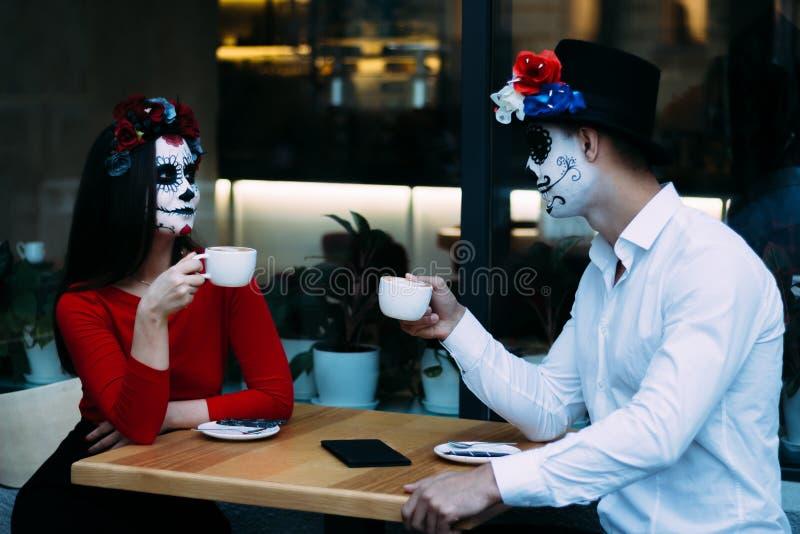 Un couple, crâne de port compenser Tout le jour d'âmes Maquillage de crâne de sucre de garçon et de fille peint pour Halloween re photos libres de droits