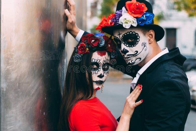 Un couple, crâne de port compenser Tout le jour d'âmes Maquillage de crâne de sucre de garçon et de fille peint pour la position  image stock