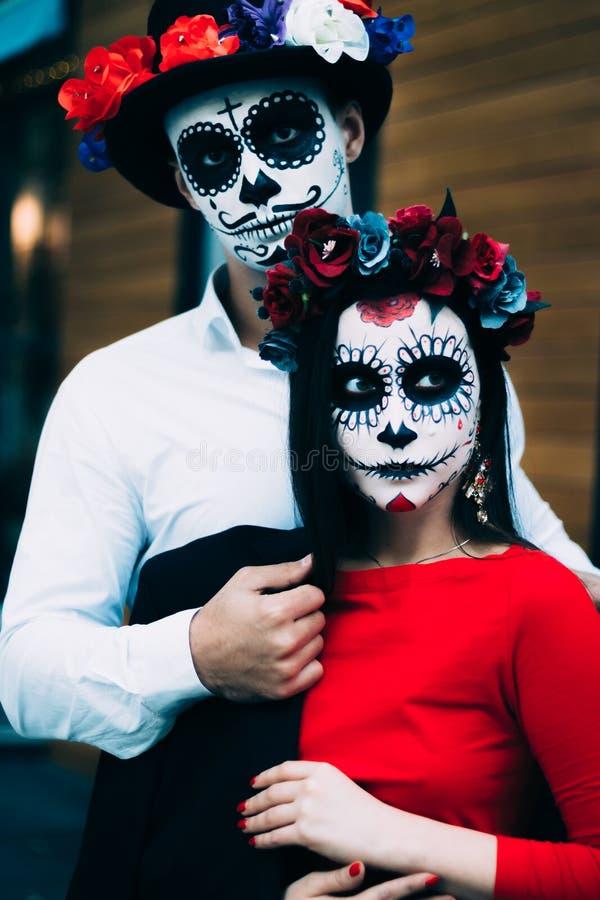 Un couple, crâne de port compenser Tout le jour d'âmes Maquillage de crâne de sucre de garçon et de fille peint pour la position  photo stock