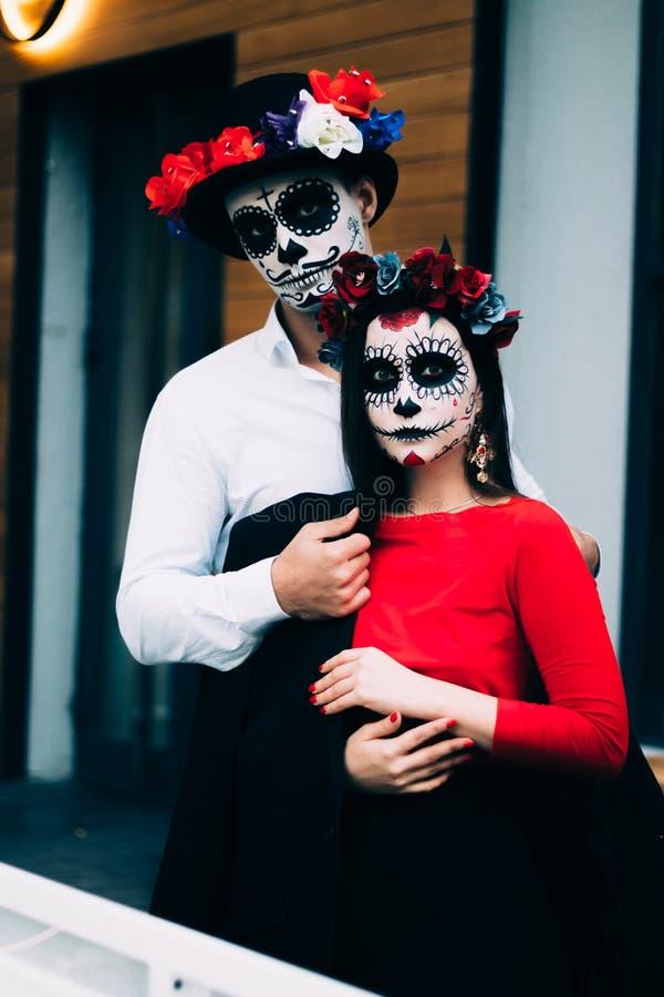 Un couple, crâne de port compenser Tout le jour d'âmes Maquillage de crâne de sucre de garçon et de fille peint pour la position  photo libre de droits