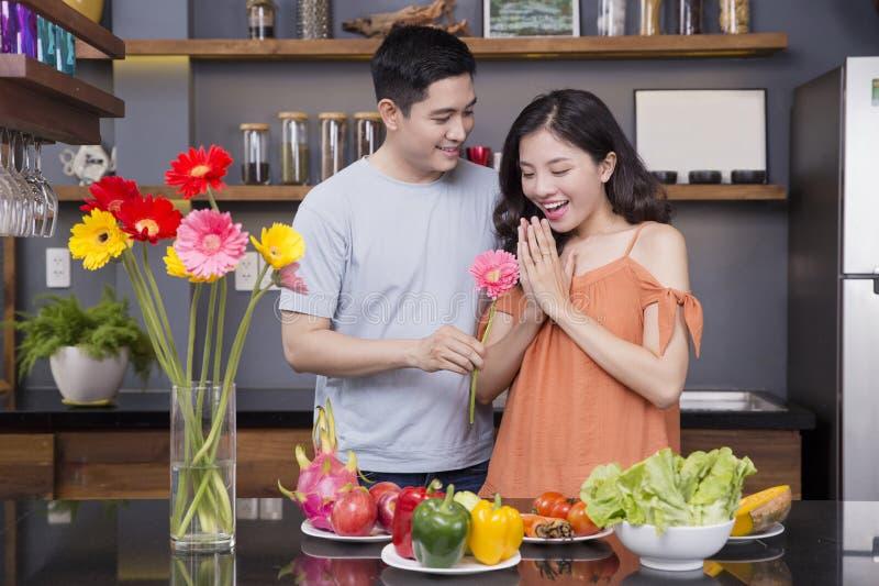Un couple dans la cuisine avec beaucoup de fruits et légumes image libre de droits