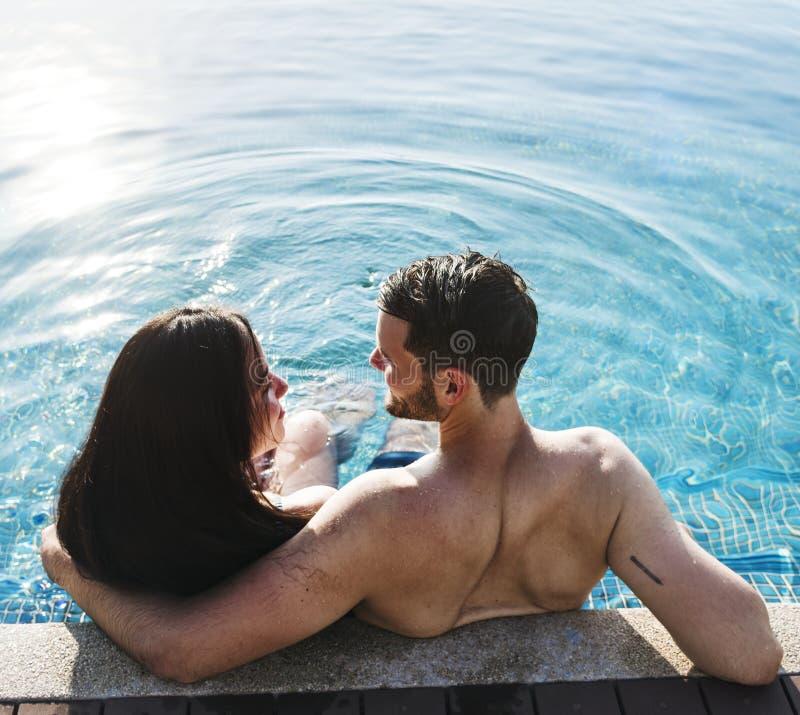 Un couple dans la piscine passant le temps ensemble images stock