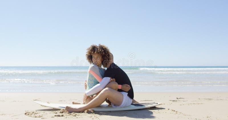 Un couple embrassant sur une planche de surf images libres de droits