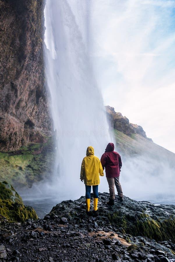 Un couple en civil illumine une cascade islandaise image libre de droits
