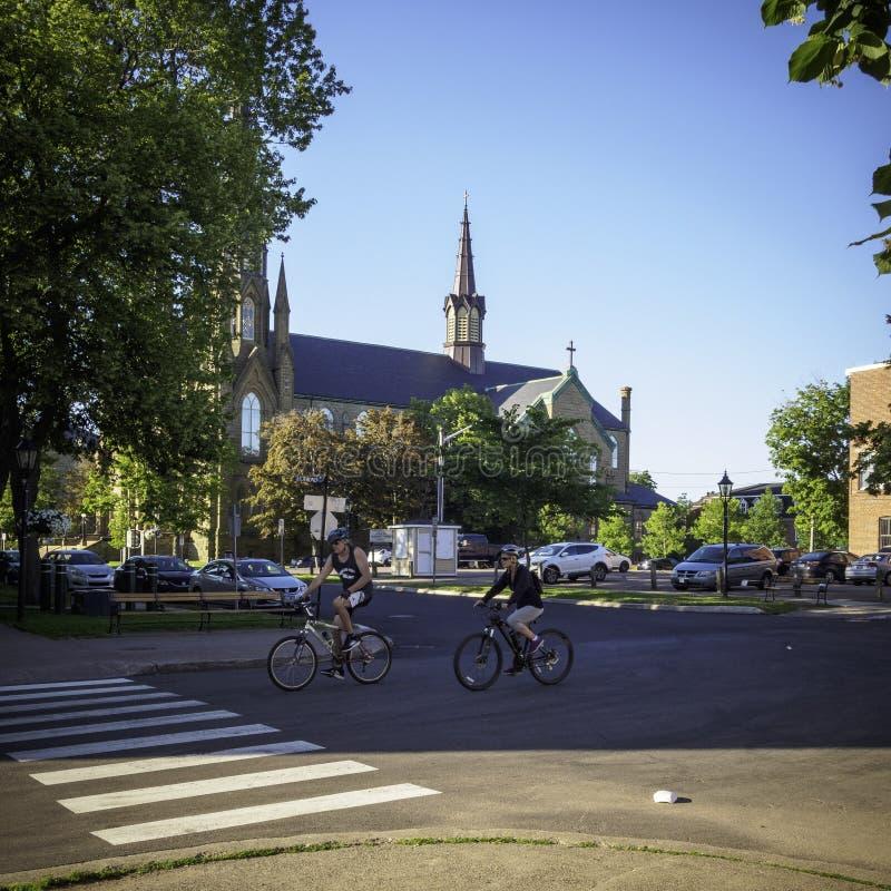 Un couple faisant un cycle à Charlottetown pendant le matin avec la chaise de la basilique de StDunstan à l'arrière-plan photos libres de droits
