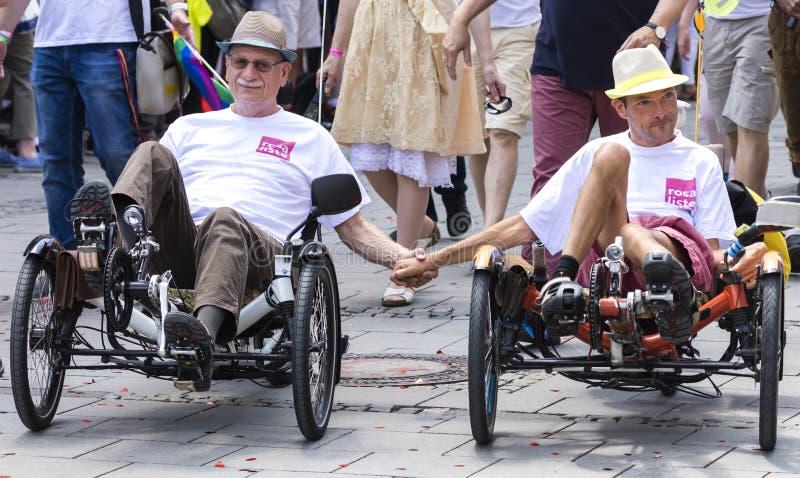 Un couple gai montant le tricycle couché et tenant des mains assistant au défilé de Gay Pride à Munich photographie stock