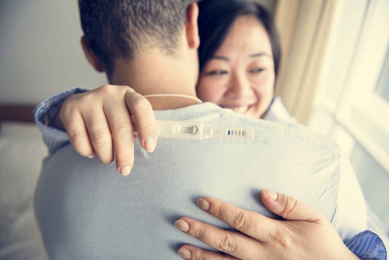 Un couple heureux au sujet du résultat d'essai de grossesse images stock