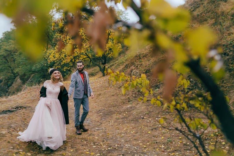 Un couple heureux marche sur une traînée dans des jeunes mariés de forêt d'automne avec des dreadlocks regarde l'un l'autre dessu image stock
