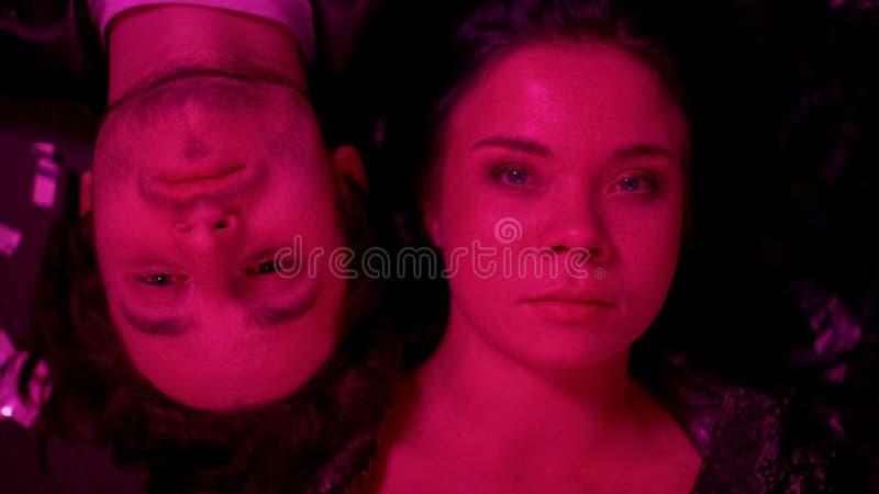 Un couple insouciant se reposant à la fête rave, allongé sur le toit, lumière rouge, mauvais traitements images libres de droits