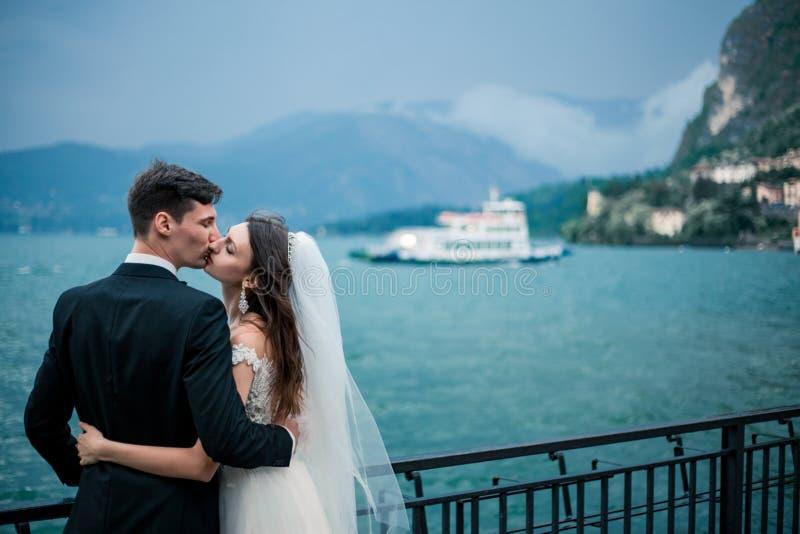 Un couple l'épousant embrassant sur le fond d'un lac et des montagnes image libre de droits