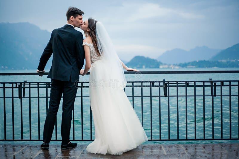 Un couple l'épousant embrassant sur le fond d'un lac et des montagnes photographie stock