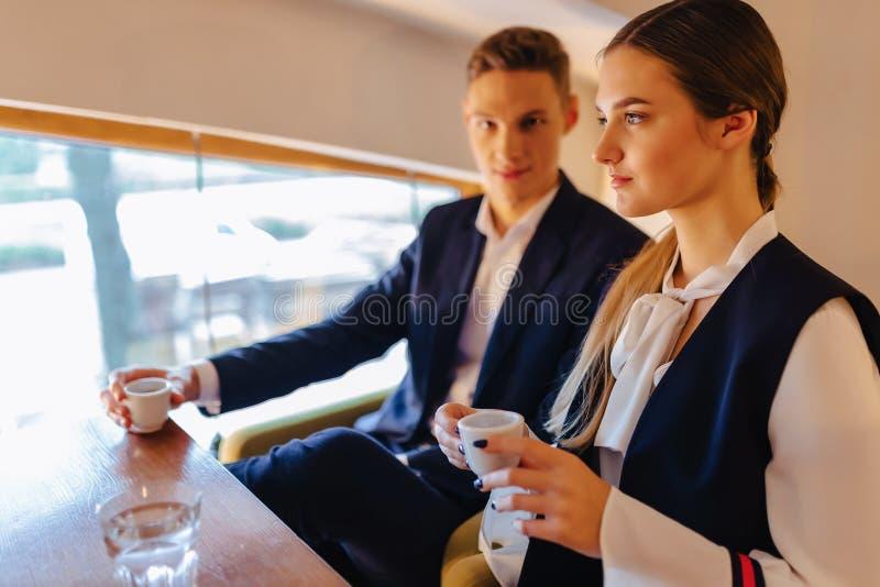 Un couple ?l?gant boit du caf? de matin au caf?, aux jeunes hommes d'affaires et aux ind?pendants photo stock