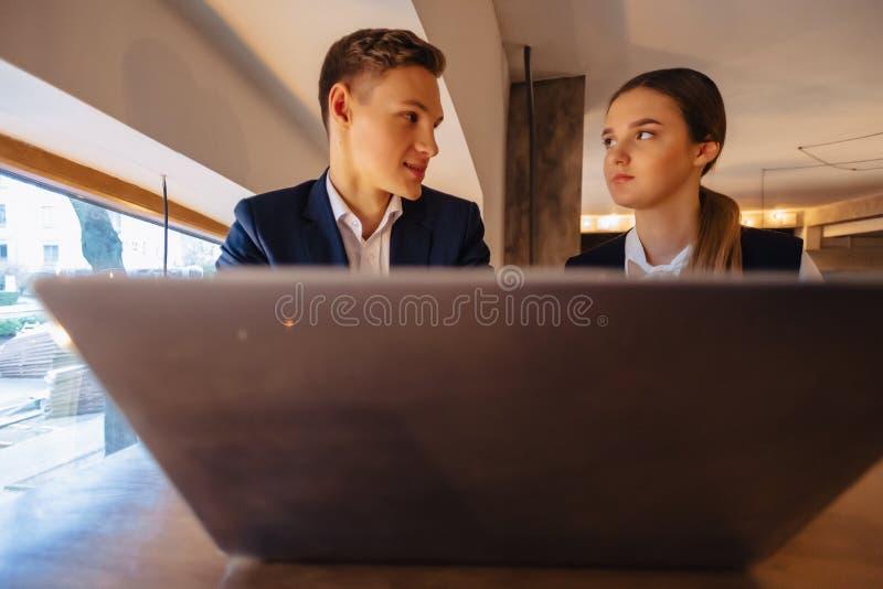 Un couple ?l?gant boit du caf? de matin au caf? et fonctionne avec un ordinateur portable, de jeunes hommes d'affaires et des ind images stock