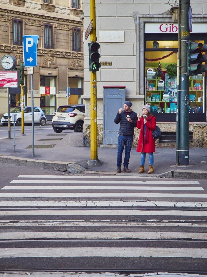 Un couple mangeant la crème glacée attendant pour croiser un passage piéton de voisinage magenta de Zona Milan, Italie photos stock