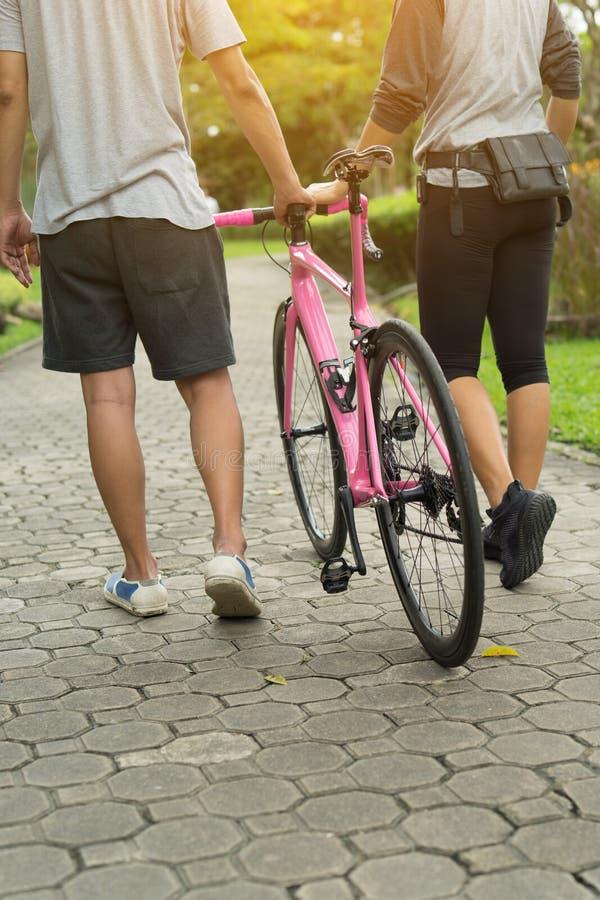 Un couple marchant avec un vélo avec amour et détend en parc images libres de droits